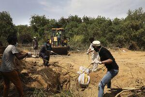 عکس/ کشیدن جسد قربانیان کرونا با طناب تا داخل قبر